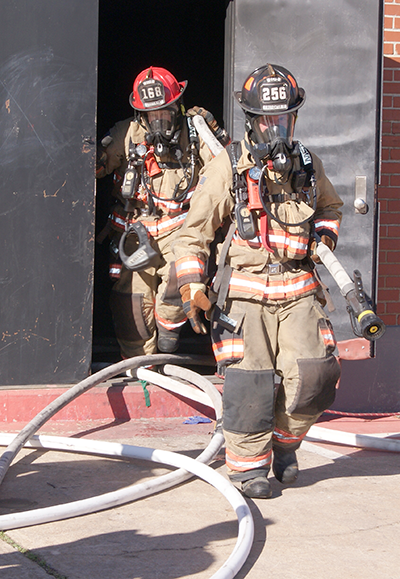 Firefighters carrying hoses out of building