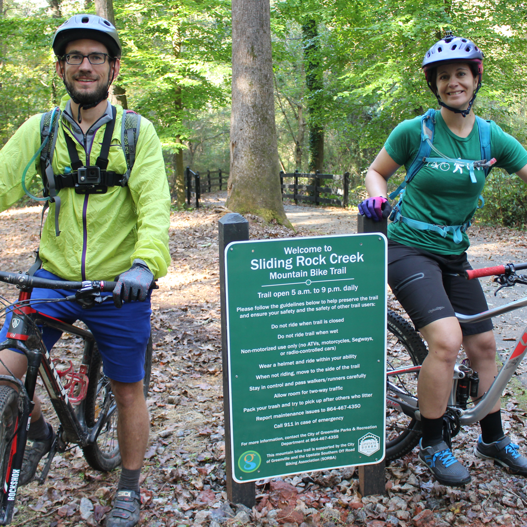 Two mountain bikers at the entrance to the Sliding Rock Creek Trail.