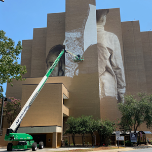 Building showing large-scale mural in progress along College Street
